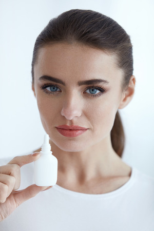 healthcare portrait: Illness Prevention. Portrait Of Beautiful Healthy Young Woman Holding Nasal Drops Indoors. Closeup Of Female With Bottle Of Nasal Spray, Cold And Sinus Medicine In Hands. Healthcare. High Resolution