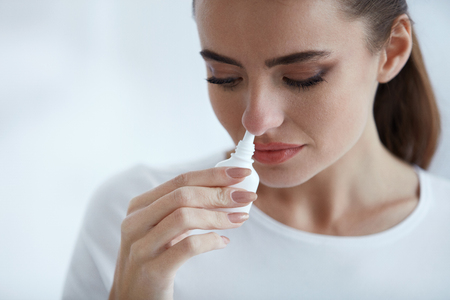 Illness And Sickness. Closeup Of Beautiful Woman Feeling Sick Dripping Nasal Drops In Blocked Nose. Portrait Female Sprays Cold And Sinus Medicine In Runny Nose. Sinusitis treatment. High Resolution Stock fotó - 75263388