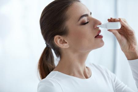 Ziekte en ziekte. Close-up van mooie vrouw gevoel ziek druipende neusdruppels in geblokkeerde neus. Portret Vrouwelijke Sprays Koud En Sinus Geneeskunde In Loopneus. Sinusitis behandeling. Hoge resolutie