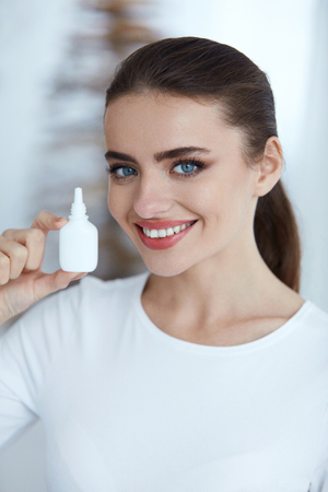 healthcare portrait: Healthcare. Closeup Of Beautiful Happy Healthy Woman Holding Nasal Spray In Hand. Portrait Of Smiling Young Female Model With Nasal Drops Indoors. Health Concept. High Resolution Stock Photo