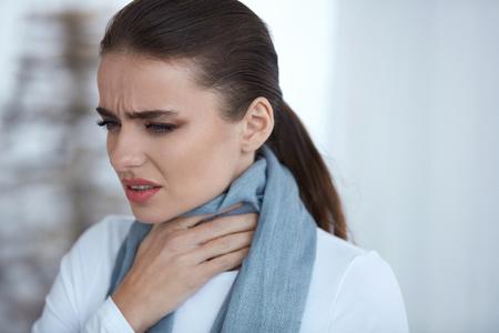 Keelpijn. Close-up van mooie ongezonde jonge vrouw In sjaal gevangen koude of griep, gevoel pijn in de keel. Portret van ziek vrouwtje met de hand aanraken hals binnenshuis. Seizoensziekte. Hoge resolutie Stockfoto