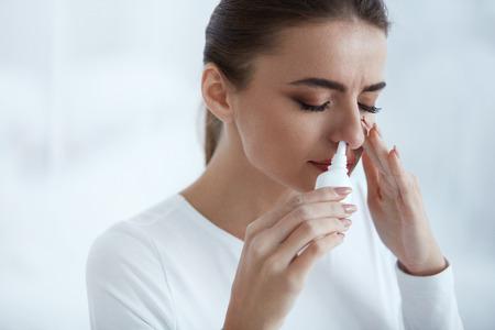 Koude. Portret van mooie jonge vrouw snuiven Neusspray Sluiten een neusgat. Close-up van vrouwelijke gevoel ziek met het runnen van neus met behulp van sinus medicatie voor geblokkeerde neus. Gezondheidszorg. Hoge resolutie