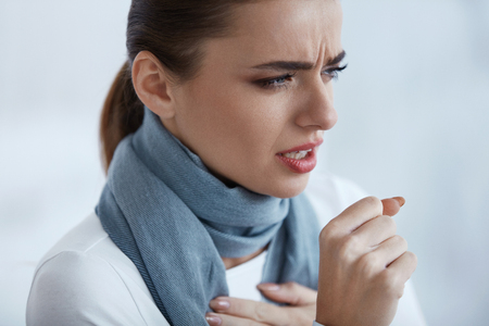 Woman Caught A Cold. Closeup Of Beautiful Sick Female In Scarf With Strong Cough Feeling Pain In Her Sore Throat. Portrait Of  Unhealthy Girl Coughing Indoors. Sickness And Illness. High Resolution