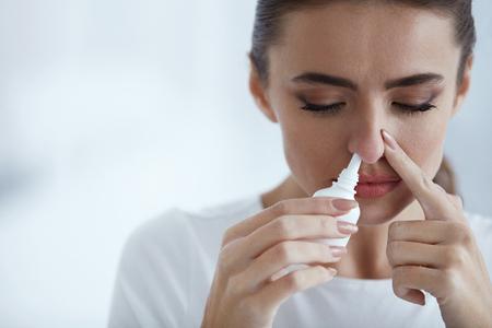 감기. 비강 스프레이 닫기 한 비공을 아름 다운 젊은 여자의 초상화. 차단 된 코에 대 한 부비동 약물을 사용 하여 코를 실행 아 프 느낌의 근접 촬영.  스톡 콘텐츠