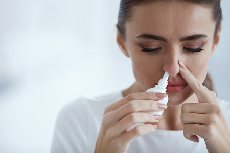 running nose: Cold. Portrait Of Beautiful Young Woman Sniffing Nasal Spray Closing One Nostril. Closeup Of Female Feeling Sick With Running Nose Using Sinus Medication For Blocked Nose. Healthcare. High Resolution