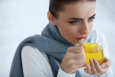 warming therapy: Beautiful Sick Woman Drinking Medicine From Cold And Flu. Closeup Of Young Female In Scarf Drinking Hot Tea. Portrait Of Girl Feeling Cold, Holding Big Cup Of Yellow Warm Drink. High Resolution Stock Photo