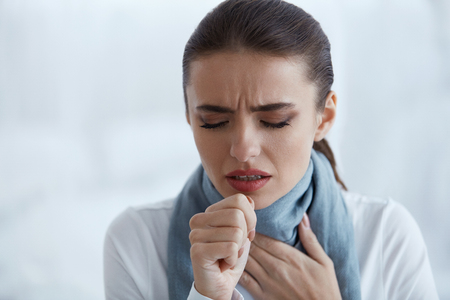 Cough. Closeup Of Beautiful Young Woman Caught Cold Or Flu Illness, Having Sore Throat And Coughing With Hand Near Mouth. Portrait Of Unhealthy Girl In Scarf Feeling Pain In Throat. High Resolution Stock Photo