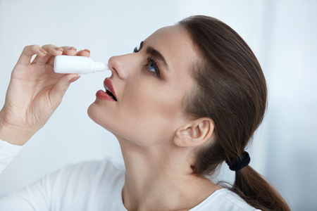 Healthcare. Closeup Of Beautiful Young Woman Using Nasal Spray Indoors. Portrait Of Sick Girl Having Flu Spaying Medical Nasal Drops For Blocked Running Nose. Illness And Sickness. High Resolution Stock Photo