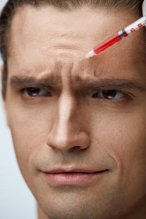 整形手術。ハンサムな男性作るのクローズ アップの顔顔顔美容注射を受けて皮膚を持ち上げます。美容師は、患者の皮膚に赤い液体を注入します。