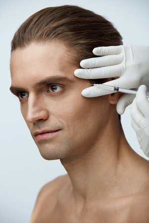 Face Lifting. Closeup Of Doctors Hands Injecting Hyaluronic Acid Into Mans Facial Skin. Portrait Of Handsome Male Receiving Skin Lift Injection, Beauty Injections. High Resolution Фото со стока