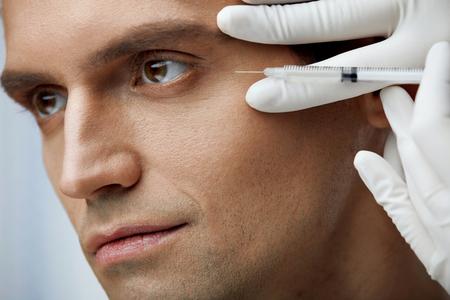 顔の美しさの治療。頬骨でヒアルロン酸注入を受けてハンサムな男性の肖像画。注射器を持って、男の顔に注射を持ち上げる皮膚の手のクローズ ア 写真素材