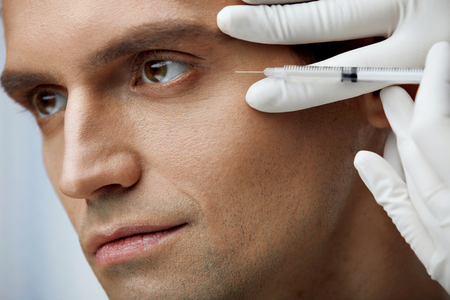 Facial Beauty Treatment. Portrait Of Handsome Male Receiving Hyaluronic Acid Injection In Cheekbone. Closeup Of Hands Holding Syringe, Doing Skin Lifting Injections On Mans Face. High Resolution