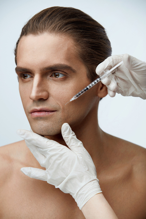 Face Procedure. Portrait Of Handsome Young Man Receiving Facial Lifting Injections. Closeup Of Beautician Hands Doing Cosmetic Injection On Male Cheekbone. Beauty Treatment Concept. High Resolution Stock Photo