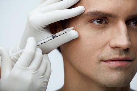 顔射出。ハンサムな男性の肌にヒアルロン酸注入を行う美容師のクローズ アップ。顔美容治療、充填剤の注射を受けて若い男性の肖像画。美容。高