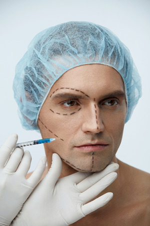 Male Plastic Surgery. Portrait Of Attractive Young Man In Medical Hat With Surgical Black Lines On Face. Closeup Of Handsome Male Patient Receiving Beauty Injection In Facial Skin. High Resolution