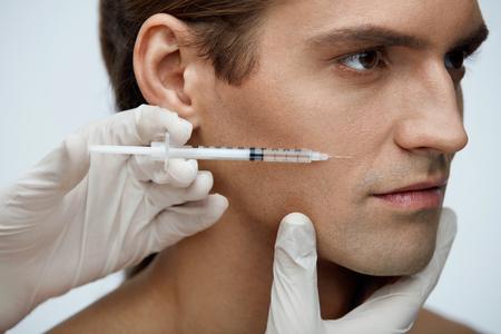 美容。美容治療室内を取得完璧な肌を持つハンサムな男の肖像画。男性の顔にフィラーの注入を注入する美容師の手のクローズ アップ。皮膚のリフトの手順。高分解能 写真素材 - 75379320