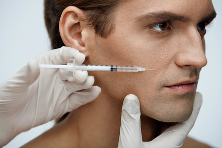 Cosmetology. Portrait Of Handsome Man With Perfect Skin Getting Beauty Treatment Indoors. Closeup Of Beautician Hands Injecting Filler Injection On Male Face. Skin Lift Procedure. High Resolution Stock Photo - 75379320