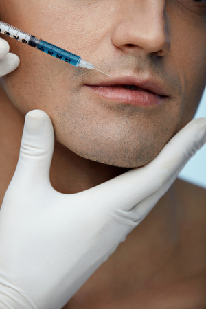 revitalization: Facial Injection. Closeup Of Beautician Doing Injection In Young Male Patient Lips. Man Face Receiving Beauty Procedure Using Filler Injections. Cosmetology And Beauty Concepts. High Resolution