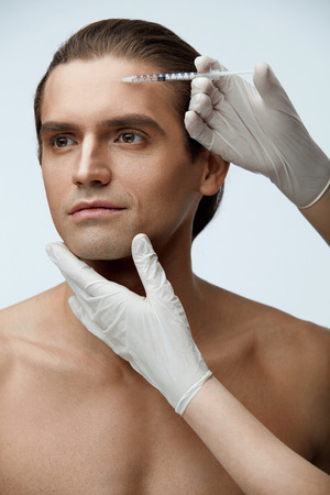 Face Lift. Closeup Of Hands Doing Hyaluronic Acid Beauty Injection In Forehead Of Handsome Mans Face. Portrait Of Male Patient Receiving Cosmetic Treatment, Facial Procedure Indoors. High Resolution