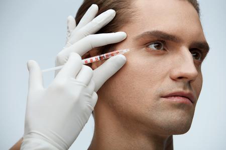 顔の美しさ。ヒアルロン コラーゲン注射を取得ハンサムな男の肖像画。男性の顔に近い透明な液体とシリンジを保持している美容師の手のクローズ