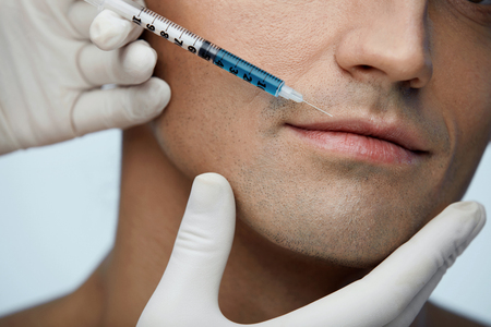 Facial Injection. Closeup Of Beautician Doing Injection In Young Male Patient Lips. Man Face Receiving Beauty Procedure Using Filler Injections. Cosmetology And Beauty Concepts. High Resolution