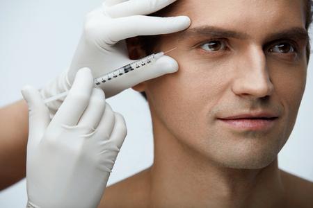 美容。美容治療室内を取得完璧な肌を持つハンサムな男の肖像画。男性の顔にフィラーの注入を注入する美容師の手のクローズ アップ。皮膚のリフ