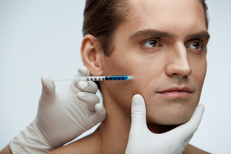 Man Plastic Surgery. Closeup Of Beautician Hands Holding Syringe With Blue Liquid Near Young Male Face. Portrait Of Handsome Man Receiving Hyaluronic Acid Injections In Facial Skin. High Resolution
