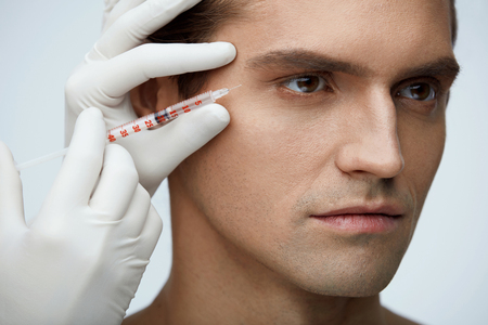 얼굴 아름다움. 콜라겐 주입 Hyaluronic 점점 잘 생긴 남자의 초상화입니다. 미용사의 근접 촬영 남성 얼굴 근처 투명 액체와 주사기를 들고 손. 피부 리프 스톡 콘텐츠