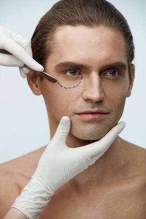 整形手術。美しい顔と手袋男性まぶた近くメスで外科医の手に黒い線でハンサムな男の肖像画。Blepharoplastic 操作、美しさの概念。高分解能