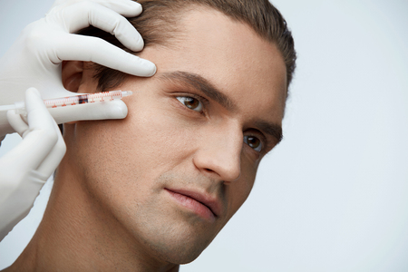 Facial Beauty. Portrait Of Handsome Man Getting Hyaluronic Collagen Injection. Closeup Of Beautician Hands Holding Syringe With Transparent Liquid Near Male Face. Skin Lifting. High Resolution Stock fotó