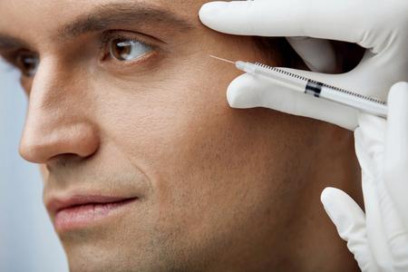 Tratamiento facial de la belleza. Retrato De Hombre Hermoso Receiving Hyaluronic Acid Injection In Cheekbone. Primer plano de las manos que sostienen la jeringa, haciendo la piel que levanta las inyecciones en la cara del hombre. Alta resolución Foto de archivo - 75360470