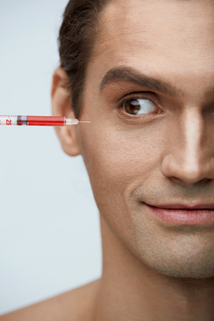 Skin Lifting. Portrait Of Handsome Smiling Man Getting Facial Beauty Injections. Closeup Of Attractive Happy Male Patient With Syringe With Red Liquid Near Face At Cosmetology Center. High Resolution Фото со стока