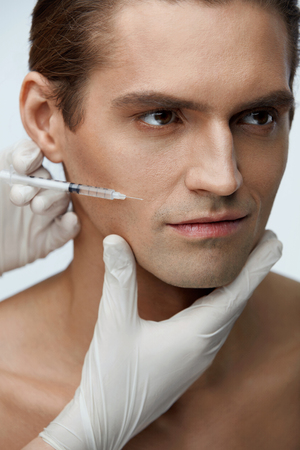 revitalization: Face Injection. Closeup Of Beautician Doing Hyaluronic Acid Injection On Handsome Man Skin. Portrait Of Young Male Receiving Facial Beauty Treatment, Filler Injections. Cosmetology. High Resolution