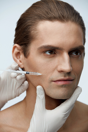 Male Beauty Injection. Portrait Of Handsome Man Receiving Hyaluronic Acid Facial Injections. Closeup Of Cosmetician Injecting Fillers Into Young Mans Face. Plastic Surgery Conceprt. High Resolution Stock Photo
