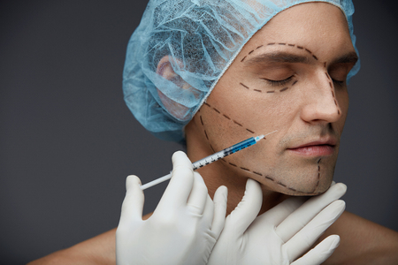 Male Face Beauty Injections. Portrait Of Handsome Man With Black Facial Lines In Blue Medical Hat Getting Filler Injection In Skin. Closeup Of Young Man Getting Skin Lifting Procedure. High Resolution