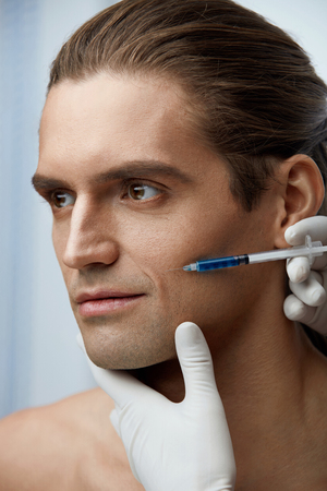 Beauty Injection. Portrait Of Handsome Sexy Man Getting Face Lifting Procedure On White Background. Close Up Doctor Hands Injecting Fillers Into Male Facial Skin. Cosmetology Concept. High Resolution Stock Photo