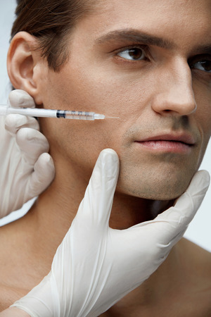 Face Injection. Closeup Of Beautician Doing Hyaluronic Acid Injection On Handsome Man Skin. Portrait Of Young Male Receiving Facial Beauty Treatment, Filler Injections. Cosmetology. High Resolution