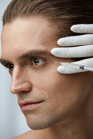 Face Lifting. Closeup Of Doctors Hands Injecting Hyaluronic Acid Into Mans Facial Skin. Portrait Of Handsome Male Receiving Skin Lift Injection, Beauty Injections. High Resolution Stock Photo