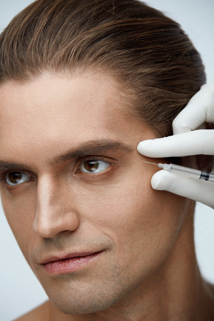 revitalization: Beauty. Closeup Of Doctors Hands In Gloves Holding Syringe With Hyaluronic Liquid Near Male Cheekbone. Portrait Of Handsome Man Receiving Cosmetic Face Injection. Facial Treatment. High Resolution