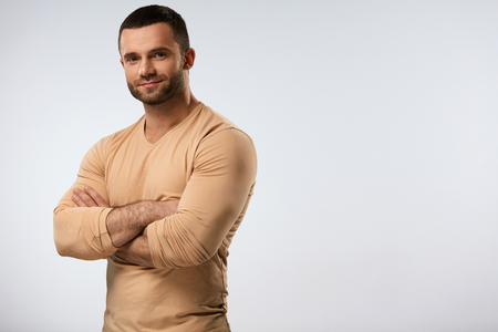 Handsome Man Portrait. Closeup Of Strong Sexy Young Male With Beautiful Face, Fit Muscular Body Standing With HIs Arms Crossed. Attractive Confident Guy On Grey Background. High Resolution Stock Photo