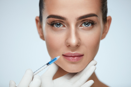 Plastic Surgery. Closeup Of Doctor Hands Doing Beauty Hyaluronic Lip Injection For Sexy Girl Lips. Portrait Of Beautiful Young Woman Getting Cosmetic Treatment Indoors. Skin Procedure. High Resolution Foto de archivo