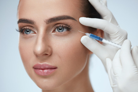 Beauty Procedure. Portrait Beautiful Young Woman Receiving Hyaluronic Acid Injection. Closeup Of Hands In Gloves Holding Syringe Near Attractive Female Face. Facial Beauty Injections. High Resolution Archivio Fotografico