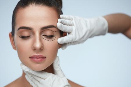 Gesichtsbehandlung. Portrait der schönen sexy Frau mit geschlossenen Augen und schwarzen chirurgischen Linien auf der Haut. Nahaufnahme der Hände berühren junge weibliche Gesicht. Plastische Chirurgie Konzept. Hohe Auflösung Standard-Bild - 75849472