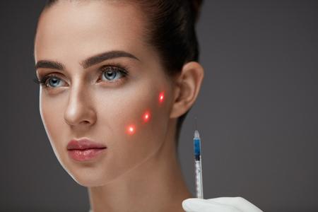 Iniezione di bellezza. Fronte di bella donna con punti laser rossi sulla pelle che riceve iniezioni della pelle del viso. Primo piano di mano con la siringa che fa la puntura ialuronica. Trattamento cosmetico. Alta risoluzione Archivio Fotografico - 75849476