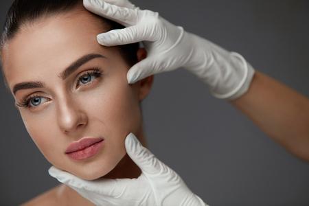 美容女性の顔。肖像完璧なメイク、滑らかな柔らかい健康な皮膚と美しい少女。若い女性の顔の皮膚に触れる手袋でメークアップ アーティストの手