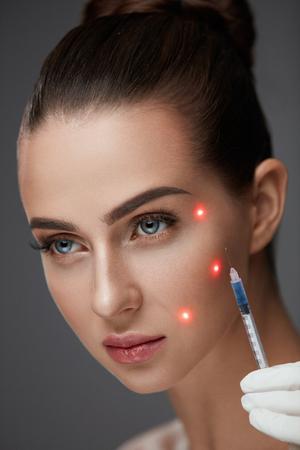 スキンケア。セクシーな若い女性患者の顔近くシリンジを押し手のクローズ アップ。ヒアルロン酸、肌のリフト注射を受けて美しい女性の肖像画。 写真素材