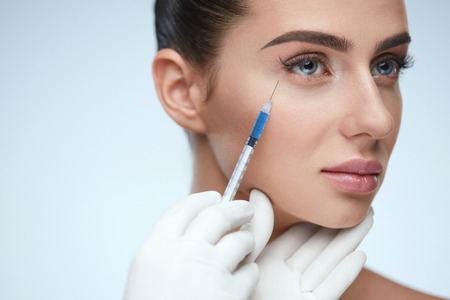 Beauty Procedure. Portrait Beautiful Young Woman Receiving Hyaluronic Acid Injection. Closeup Of Hands In Gloves Holding Syringe Near Attractive Female Face. Facial Beauty Injections. High Resolution Stock Photo