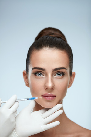 Beauty Injection. Closeup Of Doctor Hands With Syringe Near Female Face. Portrait Of Beautiful Woman With Soft Skin, Perfect Makeup Receiving Facial Skin Lifting Treatment, Injections. High Resolution