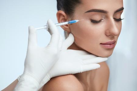化粧品の治療。クローズ アップ美容師手をやって顔肌の女性の顔を持ち上げる注入。屋内で美容の手順を受け取って目を閉じて美しい女性。整形手 写真素材