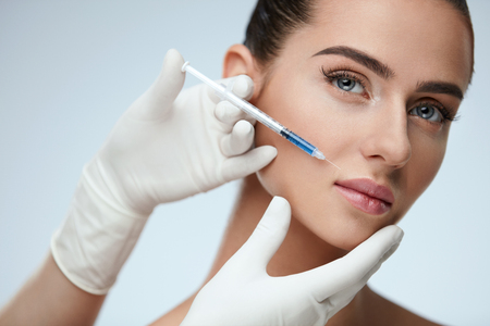 Plastic Surgery. Closeup Of Doctor Hands Doing Beauty Hyaluronic Lip Injection For Sexy Girl Lips. Portrait Of Beautiful Young Woman Getting Cosmetic Treatment Indoors. Skin Procedure. High Resolution 스톡 콘텐츠